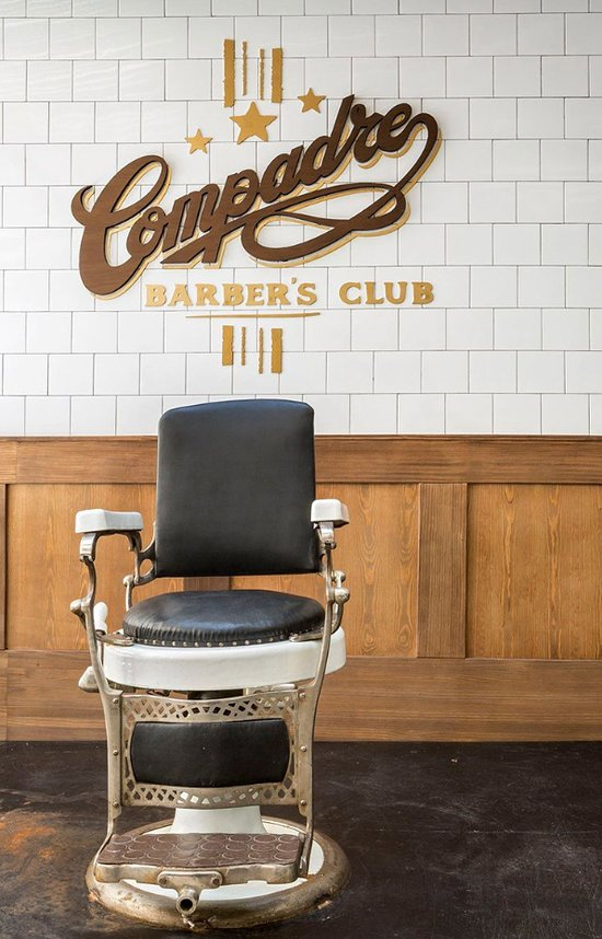 Sit down in the chair to get a haircut or shave at Compadre Barbers Club