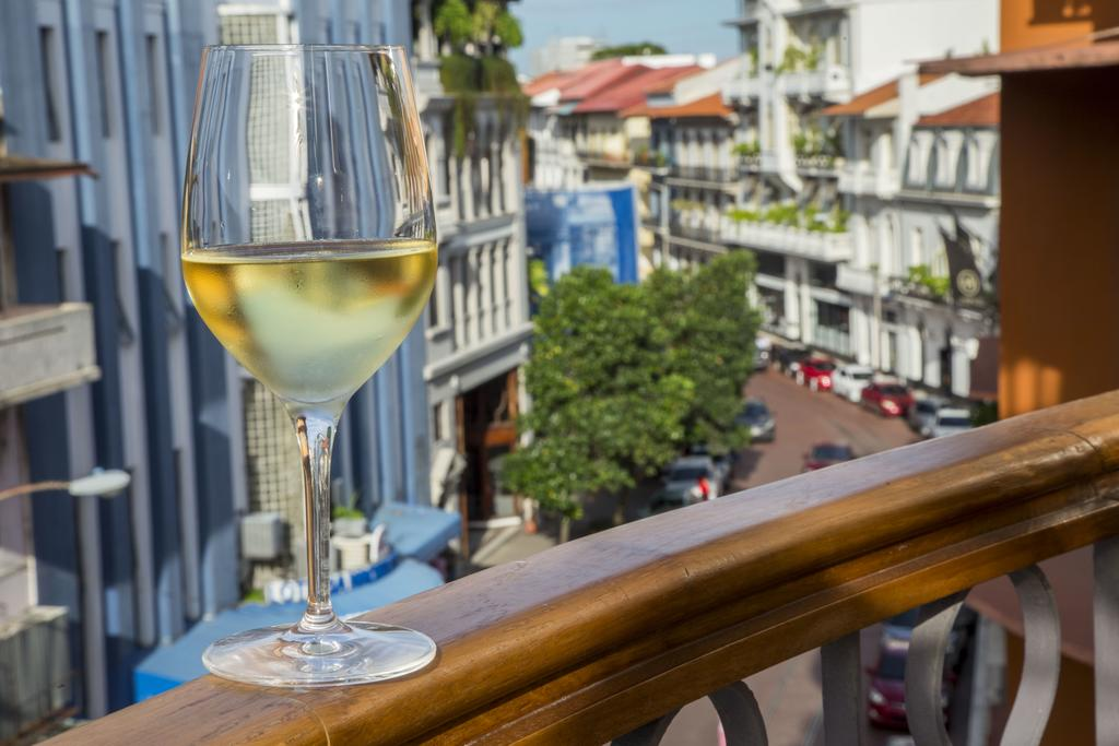 White wine glass sitting on the balcony at La Concordia Boutique Hotel looking at the American Trade Hotel