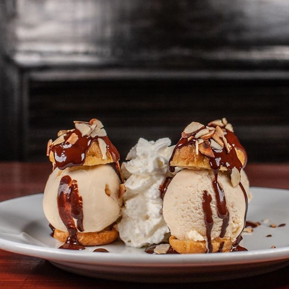 Profiteroles with ice cream, nuts, chocolate sauce and whipping cream