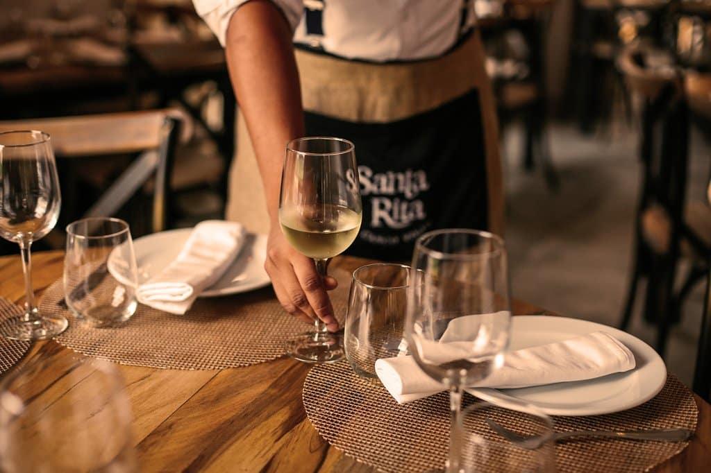 Servidor colocando vino blanco sobre la mesa en el restaurante Santa Rita Casco Viejo