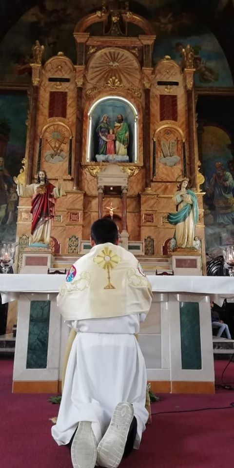 Priest praying in front of the altar of the Church of Santa Ana