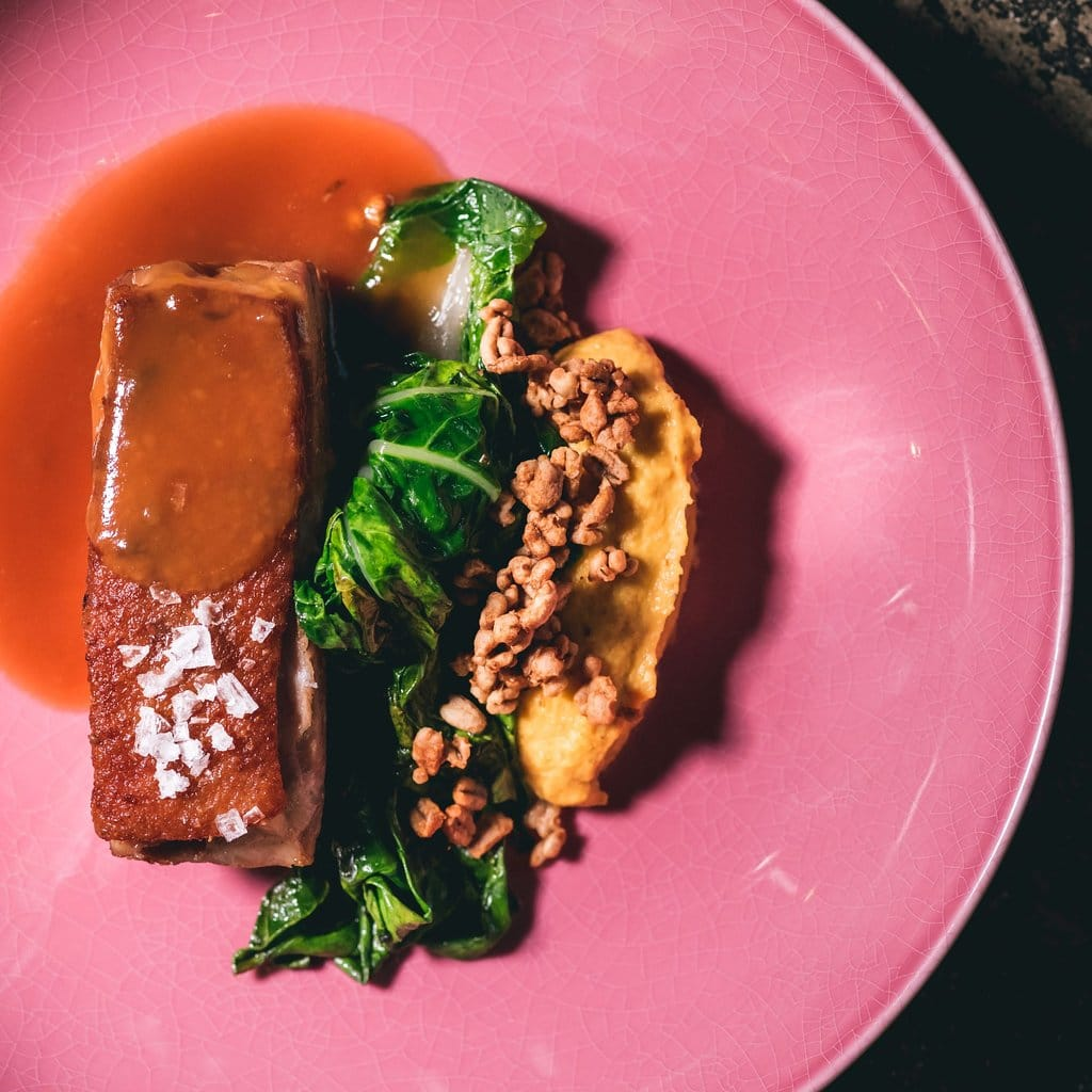 """Pato """"bocato di cardinal"""" con una nube de palmito, salsa de ajo negro fermentado y repollo chino salteado en Restaurante Caliope."""