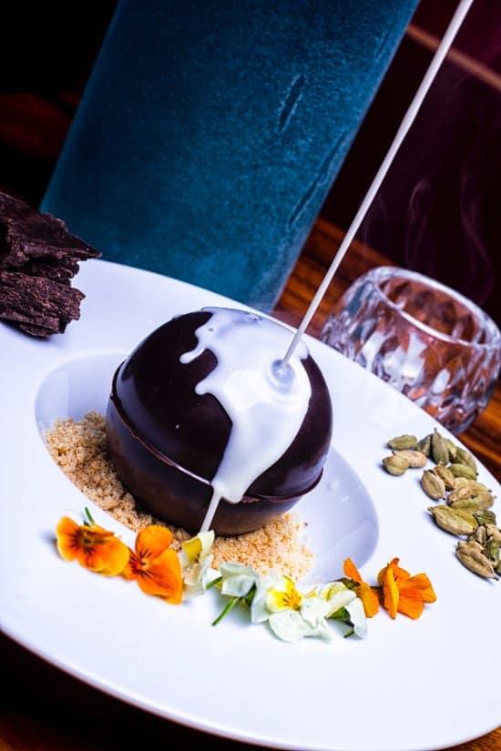 """Postre """"la sorpresa"""" que es una esfera de chocolate rellena mousse de queso mascarpone, crumble y crema de vainilla con cardamomo."""