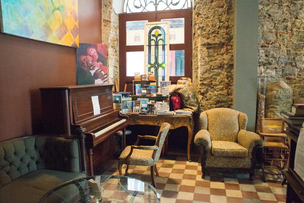 Hay un piano y sofás en la esquina de la Casa Sucre Coffeehouse.