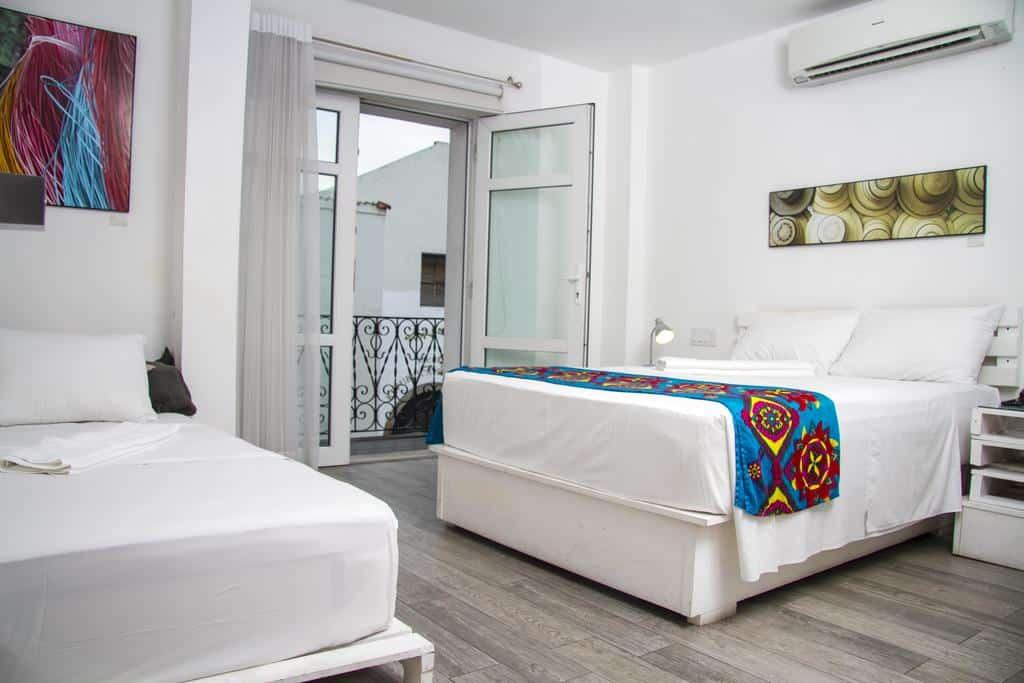 Habitación con dos camas y balcón en Gatto Blanco Party Hotel