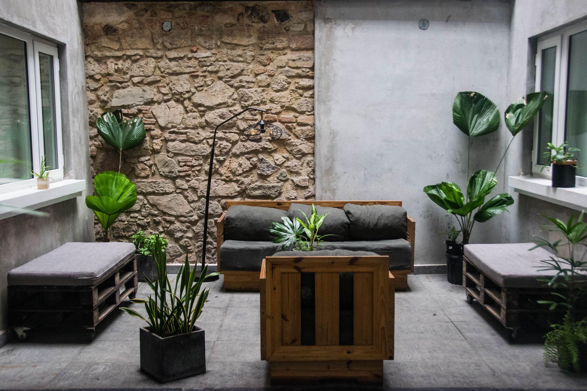 área común con muebles de paleta y plantas en Gatto Blanco Party Hotel