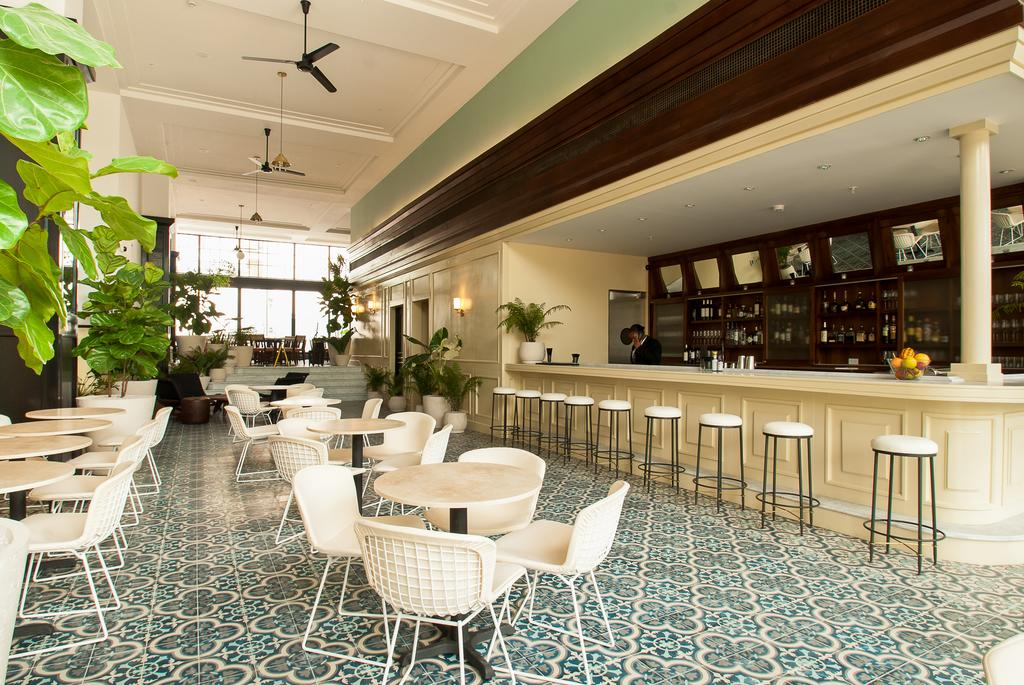 Lobby bar with stools and tables at the American Trade Hotel