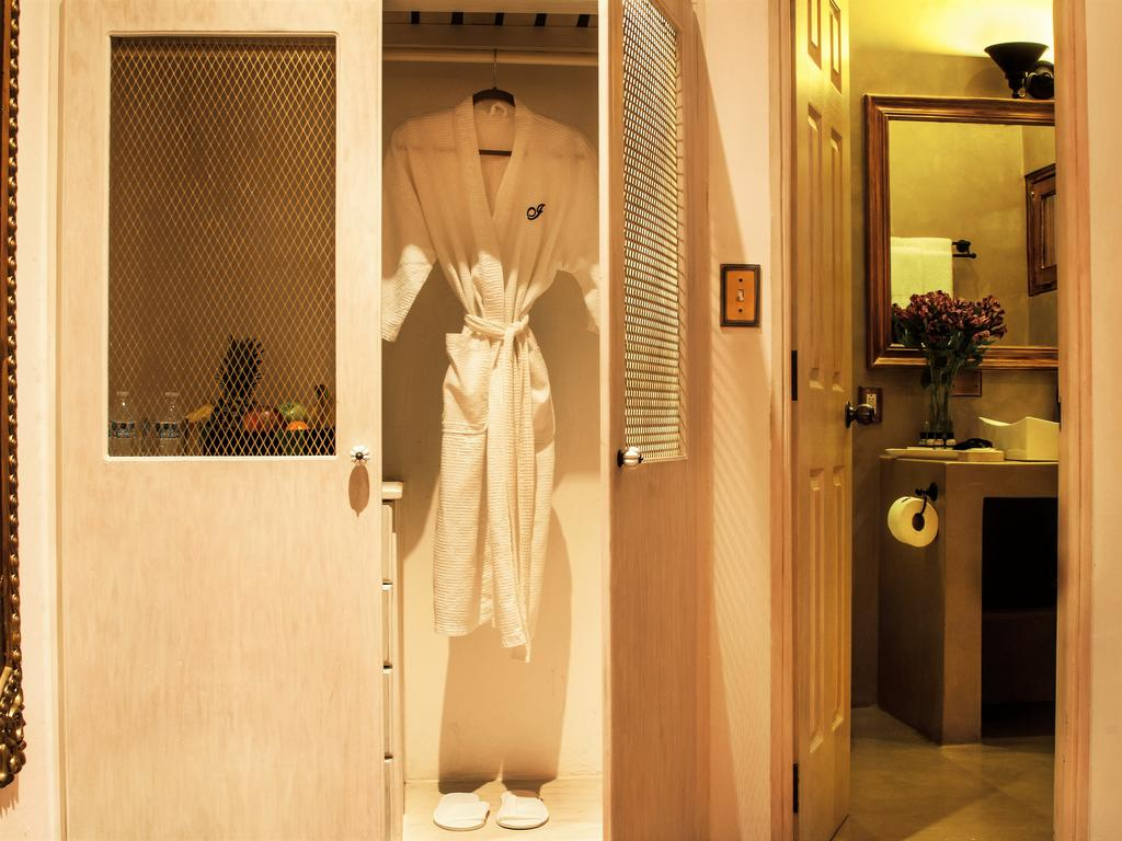 closet with robe and bathroom of La Isabela Suites