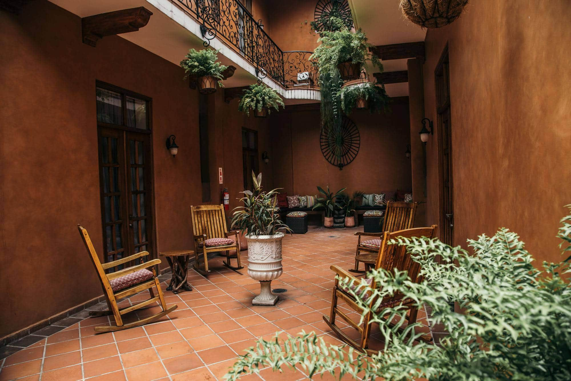 internal Spanish style courtyard with rocking chairs and plants in La Isabela Suites