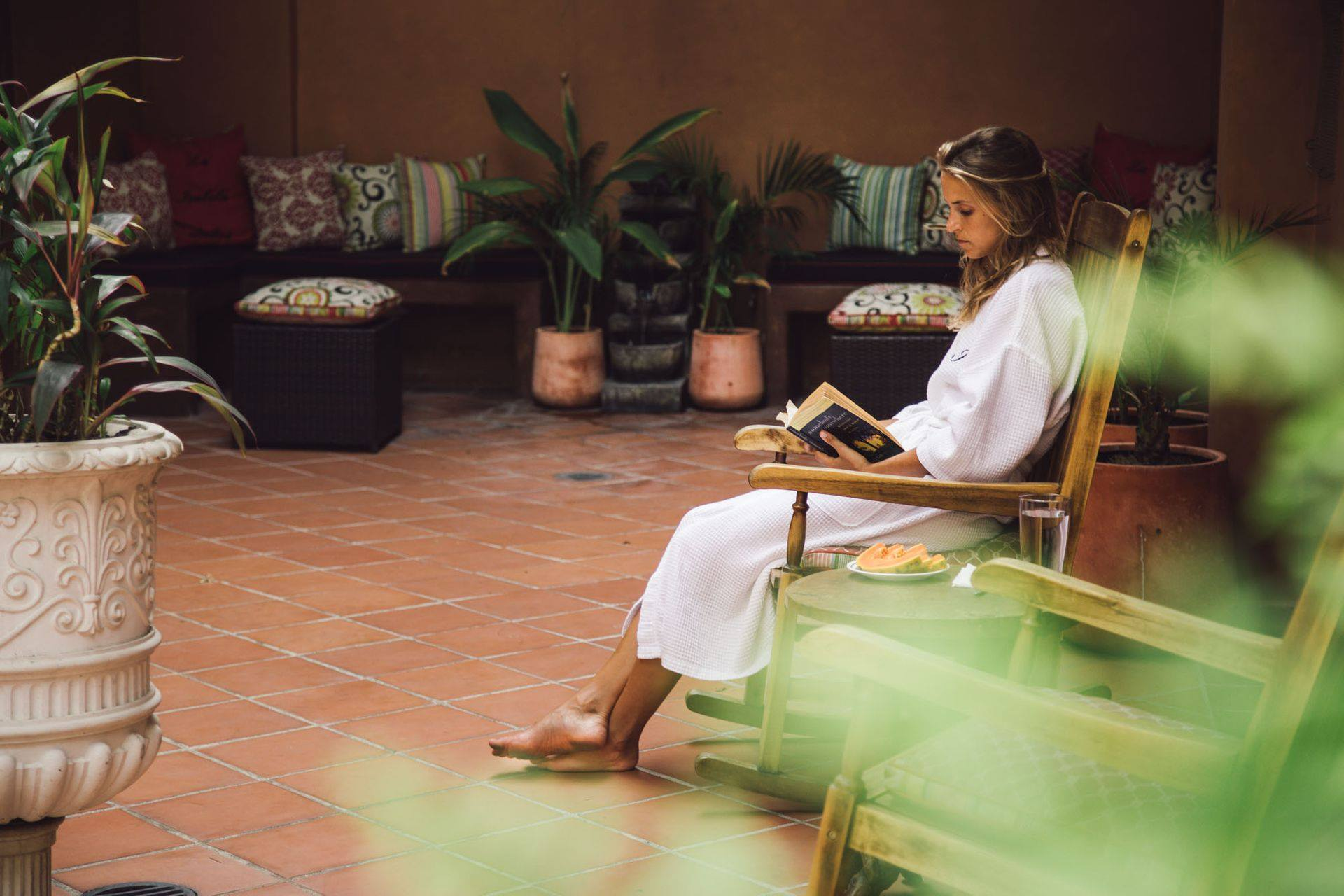woman reading in a rocking chair in the courtyard of La Isabela Suites