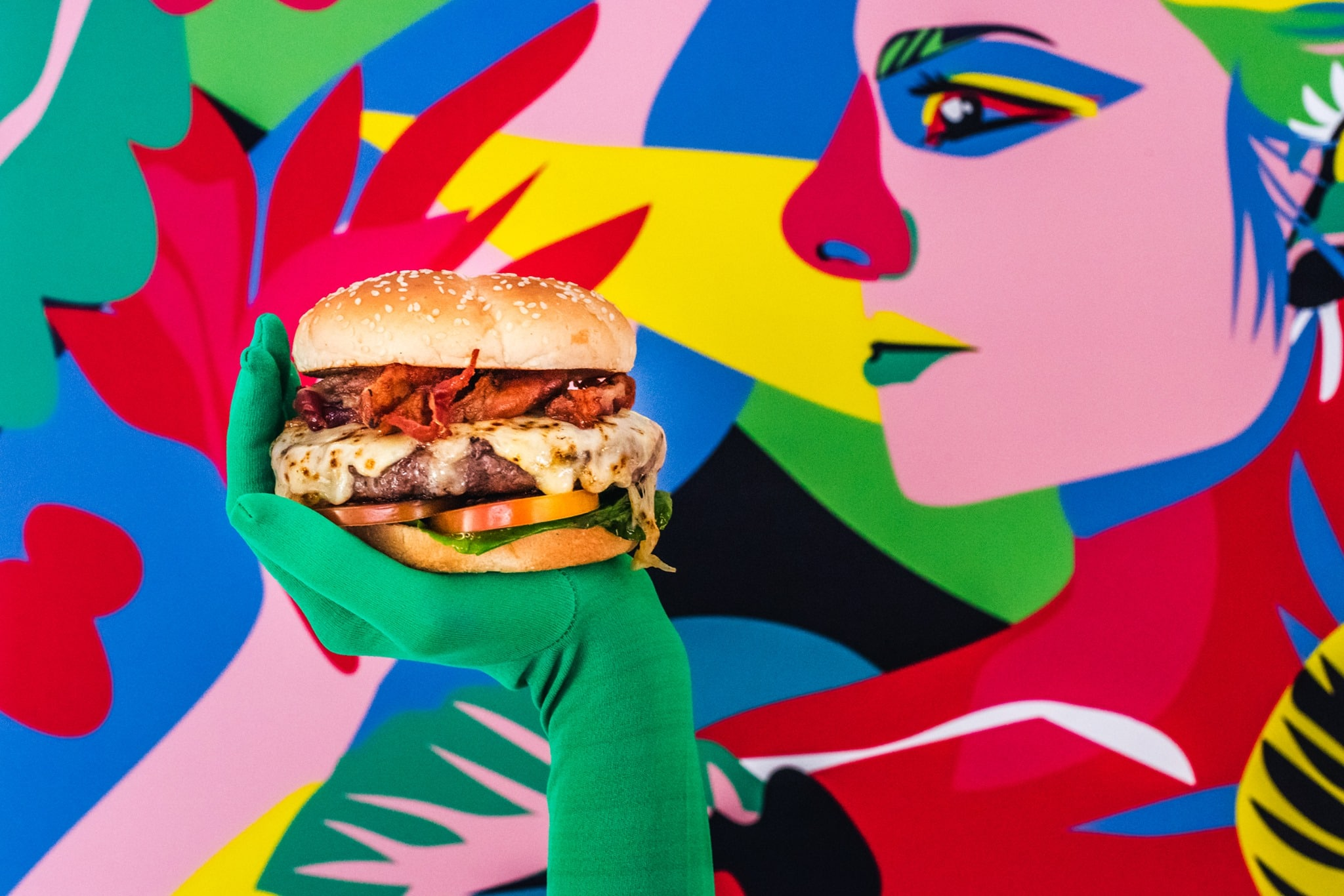 Hamburger placed on a woman's hand with a mural behind in Tantalo Kitchen