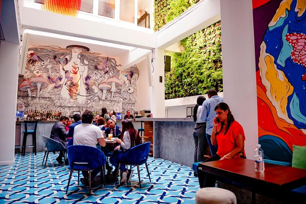 Atrio con bar y pared verde en el Hotel Tantalo en Casco Viejo