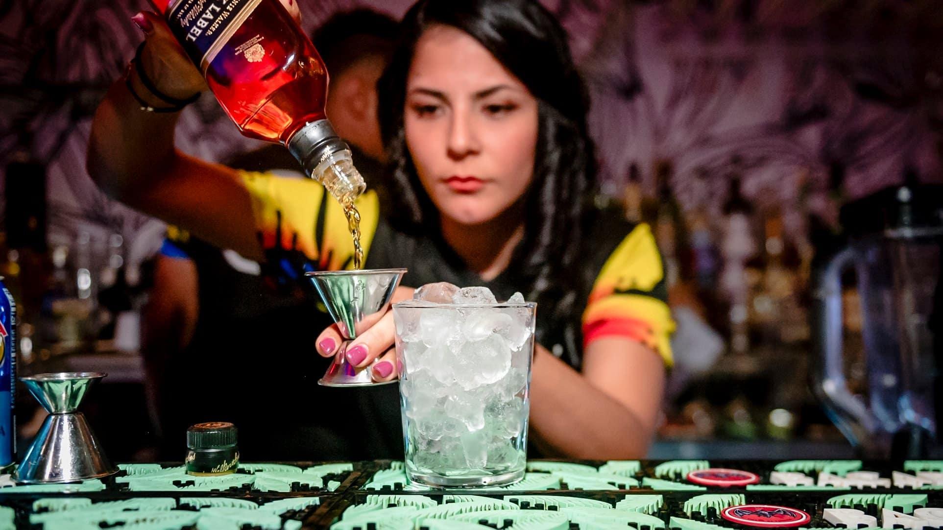 Bartender serving whiskey drink at Tantalo Rooftop Bar