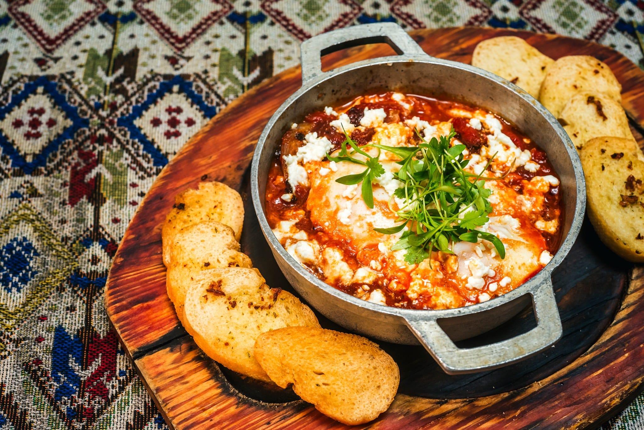 Shakshuka israelí, huevos en un recipiente de metal con pan
