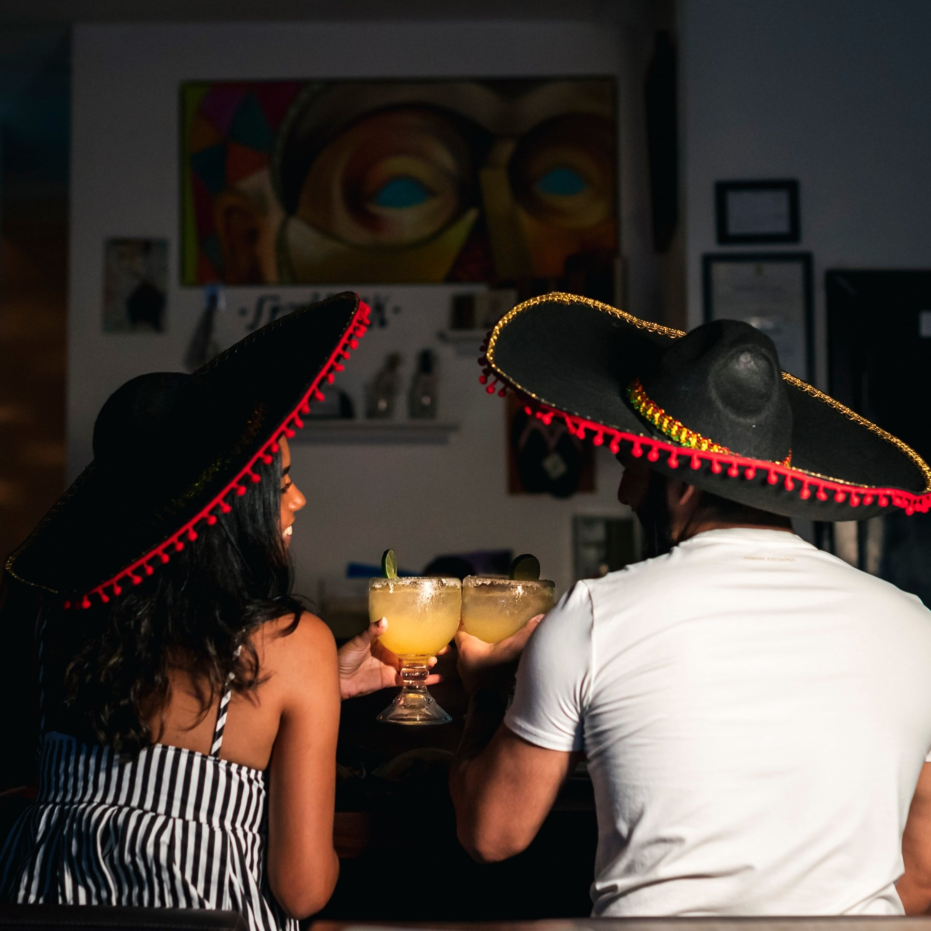 A couple toasting with margaritas and wearing mariachi hats