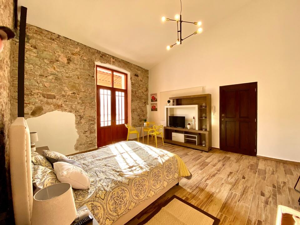 Bed and entertainment center with television at Vive Casco Antiguo in Casa Santana